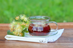 Cup with linden tea and flowers on wooden table Royalty Free Stock Image