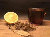 A cup of linden tea and lemon on the cutting board with black background Stock Photos