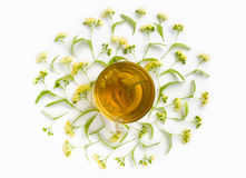 Cup of linden tea surrounded by lindens on white background. Healing Drink. Top view. Royalty Free Stock Photos
