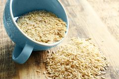 Cup of long grain brown rice. On table Royalty Free Stock Image