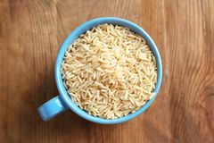 Cup of long grain brown rice. On table Stock Photo