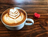 Cup of love , heart latte art coffee in white cup and red love heart. On the vintage wooden table. Love coffee love in your cup. Wake up and full fill energy Stock Photos