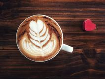 Cup of love , heart latte art coffee in white cup and red love heart. On the vintage wooden table. Love coffee love in your cup. Wake up and full fill energy Stock Image