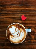 Cup of love , heart latte art coffee in white cup and red love heart. On the vintage wooden table. Love coffee love in your cup. Wake up and full fill energy Stock Photo