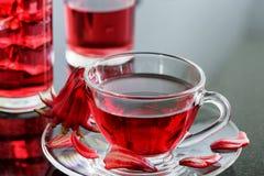 Cup of magenta hibiscus tea (rosella, karkade) on table Stock Photos