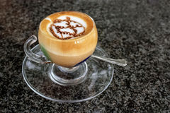 A cup of marocchino on the table. A cup of a special art of coffee marocchino in a glass cup on the dark table Royalty Free Stock Image