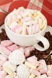 Cup of marshmallows sweet with coffee beens. Vertical composition with cup, coffee beens and marshmallows on table Stock Images