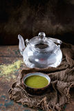 Cup of matcha tea. Ceramic cup of green matcha tea with glass teapot with hot water on wet sackcloth rag over dark wooden textured background. Healthy food. With stock photos