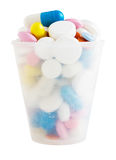 Cup for medication with colorful pills Stock Photography