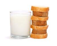 Cup Milch nahe Stapel des geschnittenen Stangenbrots stockbild