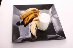 Bananas with Milk. Cup of milk with Bananas on black Tray on white background Stock Photo