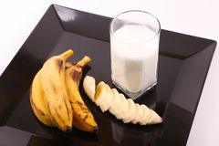 Milk with Bananas. Cup of milk with Bananas on black Tray on white background Stock Photos