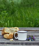 Cup of milk with bread and flower bunch Stock Images