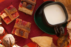 A cup of milk coffee, several pieces of homemade pie with jam, chestnuts and dry autumn leaves on a red surface Stock Photo