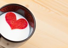 Cup of milk with decorative heart on wood table, concept of valentine day Royalty Free Stock Photos
