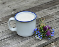 Cup of milk with flower bunch on planks Royalty Free Stock Photos
