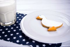 Cup of milk and ginger duckshape cookies on a white wooden table and dark blue naplin with stars. Stock Photo