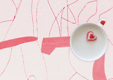 Cup of milk with heart on a geometric background. Concept Love. Red candy heart placed on the middle cup of milk on a geometric print background Royalty Free Stock Photos