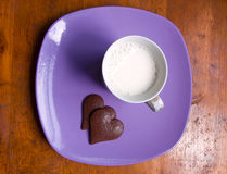 Cup of milk and heart-shaped chocolate on plate royalty free stock photography