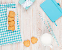 Cup of milk, heart shaped cookies, gift box and notepad Royalty Free Stock Images
