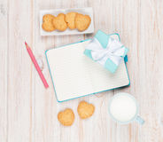 Cup of milk, heart shaped cookies, gift box and notepad Royalty Free Stock Photo