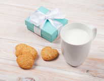 Cup of milk, heart shaped cookies and gift box Stock Photo