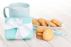 Cup of milk, heart shaped cookies and gift box Stock Images