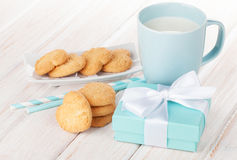 Cup of milk, heart shaped cookies and gift box Stock Photos