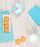 Cup of milk, heart shaped cookies and gift box Stock Photography