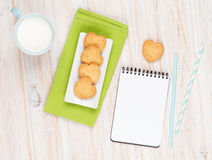 Cup of milk, heart shaped cookies and notepad Royalty Free Stock Image