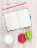Cup of milk and macarons on white wooden table with notepad Stock Photo