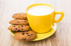 Cup of milk and oatmeal cookies with chocolate on saucer Royalty Free Stock Photography