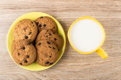 Cup of milk and oatmeal cookies with chocolate in saucer Stock Image