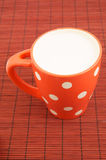 Cup of milk on placemat Stock Photos