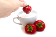 Cup of milk and strawberries. On a white background Stock Photo