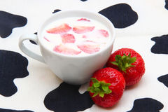 Cup of milk and strawberry. On a napkin with black spots Royalty Free Stock Image