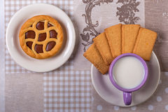 Cup of milk on table with cloth and a chocolate tart Royalty Free Stock Photos