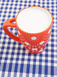 Cup of milk on tablecloth Stock Photos