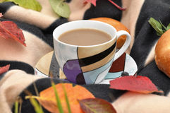 A cup of milk tea, sweet fresh buns and colorful autumn leaves on a striped warm picnic blanket Royalty Free Stock Images