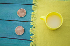 Cup of milk and two cookies, yellow scarf, turquoise surface Stock Photo