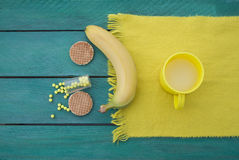 Cup of milk and two cookies, yellow scarf, turquoise surface Royalty Free Stock Images