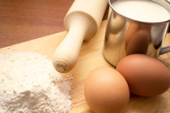Cup of milk, two eggs and flour Royalty Free Stock Photo