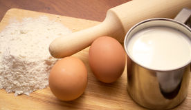 Cup of milk, two eggs and flour Royalty Free Stock Photos