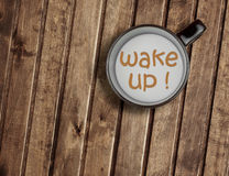 Cup of milk on wood table, with word wake up concept of breakfast Stock Image