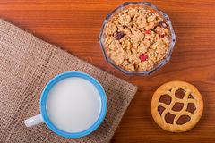 Cup of milk on a wooden table with cereals and chocolate tart Royalty Free Stock Photo