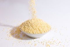 A cup of millet. Falling millet into a cup stock photo