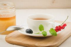 Cup of with mint tea and berries and jar of honey on a wooden tray/Cup of with mint tea and berries and jar of honey on a wooden. Tray. selective focus open royalty free stock photography