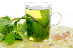 Cup of mint tea with brown cane sugar and fresh mint on a green Stock Image