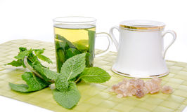 Cup of mint tea with brown cane sugar and fresh mint on a green Stock Images