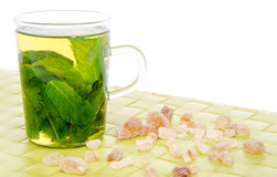 Cup of mint tea with brown cane sugar on a green place mat Royalty Free Stock Image